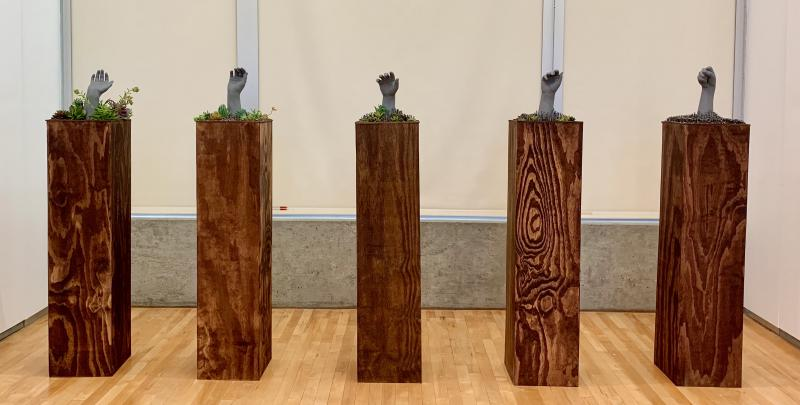 5 plaster hands surrounded by succulents and nails on wooden padestals